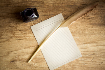 Empty paper with feather and inkpot