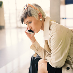 Businesswoman talking at mobile phone at Charles de Gaulle airpo