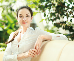 young smiling woman sitting on the sofa at home