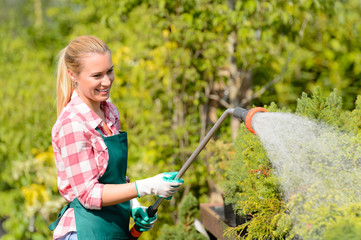 Garden center woman watering plants with hose