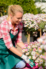 Garden center woman looking down potted flowers