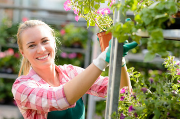 Smiling woman working in garden center sunny