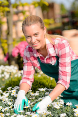 Happy female worker at garden center flowers