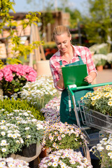 Garden center woman check flowers write notes