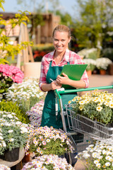 Garden center woman put potted flowers cart