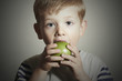 Funny Child eating apple.Little Boy.Health food. Fruits