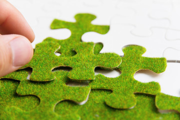 hand holding a green puzzle piece, green concept