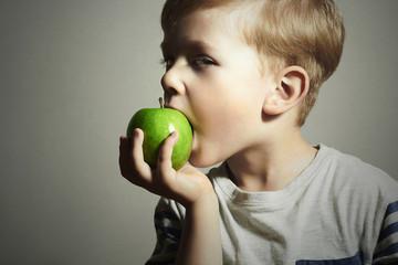 Child eating apple.Little Boy green apple.Health food.Fruits