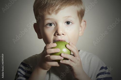 Funny Child eating apple.Little Boy.Health food. Fruits