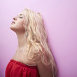 Fashion young beautiful woman. Blond girl.Pink wall