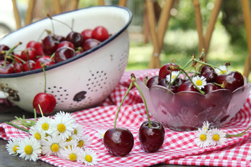 Sweet cherries on a wooden table in the garden