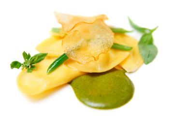 Ravioli with pesto sauce and potato chips isloated on white