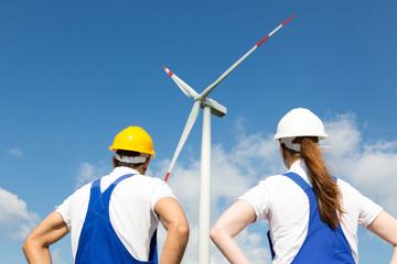 Engineers or installers posing in front of wind energy turbine