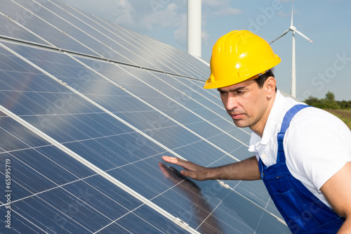 Engineer or installer inspecting solar energy panels - 65995719
