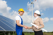 Engineers shake hands in front of solar panels and wind turbine - 65995908