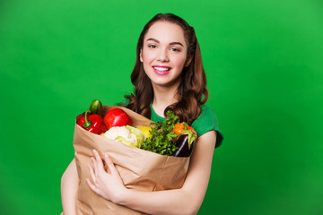 beautiful smiling woman holding grocery bag full of fresh and
