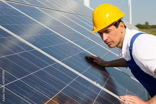 Engineer or installer inspecting solar energy panels - 65995988
