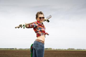 Woman holding worn rake and comfortable pose
