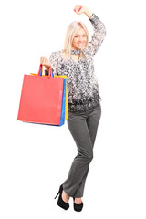 Woman holding shopping bags and gesturing success