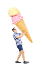 Cheerful young man carrying an enormous ice cream
