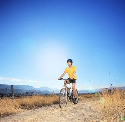 Young biker riding mountain bike in a field