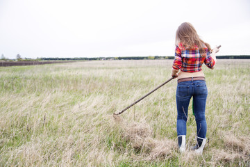 Woman rake lightly dry grass from behind