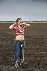 Woman and sharp shovel on cultivated field