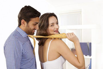 Woman in control, leads man by tie with smile