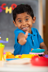 Happy Hispanic Child in School Setting Giving Thumb Up