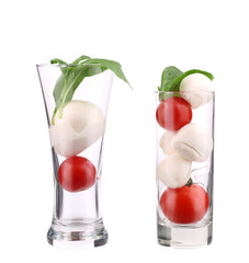 Tomatoes and mozzarella balls in glass.