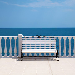 white bench and balustrade overlooking the sea