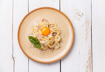 Pasta Carbonara with parmesan and yolk on white wooden backgroun