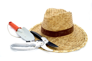 Straw hat and hand trowel and pruning shear on white