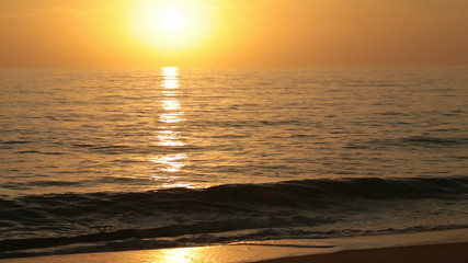 golden sunrise over the sea with small waves