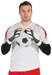 Goalkeeper in white holding ball
