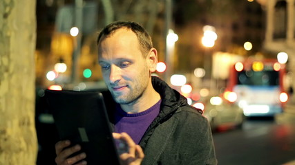 Young man with tablet computer standing in the city