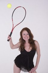 Young tennis player in black dress hits the ball