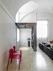 modern entrance with red chairs and marble floor
