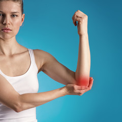Young woman suffering from elbow pain or injury.