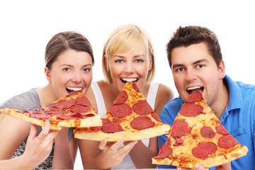 Friends eating huge pizza slices