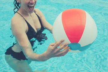 Woman in pool with beach ball