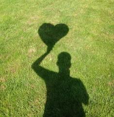 Ein Herz aus Schatten im Rasen