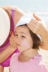 Mother applying sunblock on her daughter