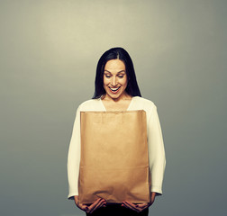 laughing woman holding paper bag