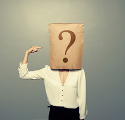 woman with paper bag pointing at question
