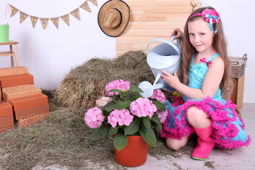 Beautiful small girl in petty skirt holding watering can