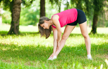 An attractive female runner stretching before her workout