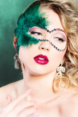 beautiful young woman in a green mysterious venetian mask
