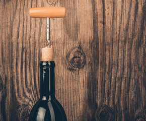 Bottle of wine and corkscrew on wooden background