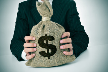 man in suit with a burlap money bag